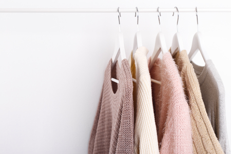 Warm knitted, autumn, winter clothes hanging on a rack, trending concept, pastel colors