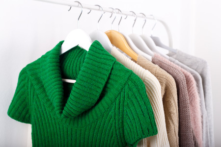 Warm knitted, autumn, winter clothes hanging on a rack, trending concept Banco de Imagens