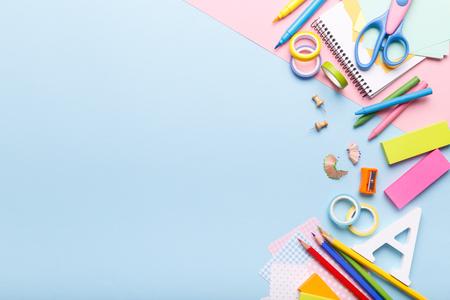 Material escolar de papelería de colores sobre fondo azul de tendencia, espacio o texto plano