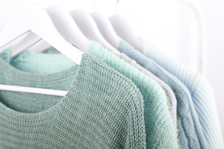 Warm knitted, autumn, winter clothes hanging on a rack, trending concept,pastel colors Banco de Imagens