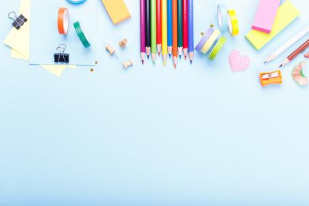 Forniture scolastiche fisse colorate su sfondo blu trend, spazio o testo piatto laici