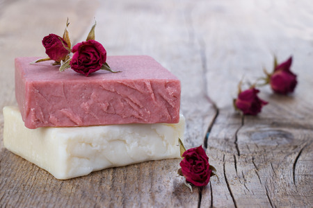 Natural hand made soap with dry pink roses on vintage wooden background spa setting Stock Photo