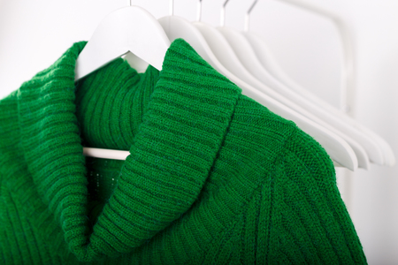 Warm knitted autumn winter clothes hanging on a rack trending green color