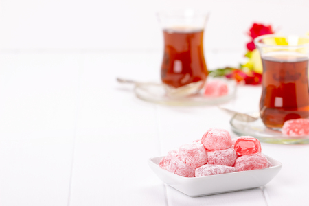 Traditional Turkish delights with oriental tea on white background
