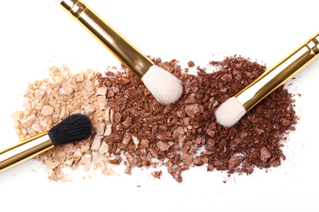 Professional makeup brushes and pastel brown eye shadows on white background