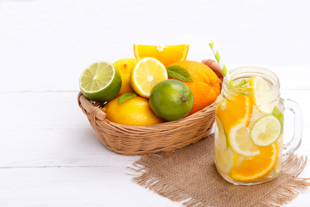 Citrus lemonade infused water with lemon lime and orange. Healthy detox drink on white wooden table Banco de Imagens