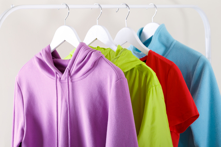 Colorful vivid sports hoodie and T-shirt hanging on a rack, trendy colors and fashion concept Banco de Imagens