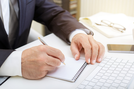 Businessman writing in a notepad, business concept close up
