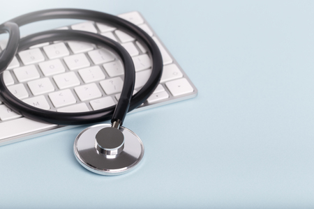 Black stethoscope and keyboard over blue background, copy space Stock Photo