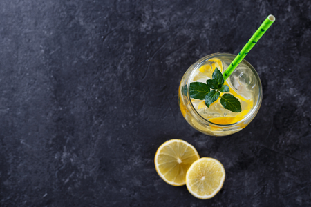 Citrus lemonade infused water with mint and lemon slices, healthy detox drink on black stone background