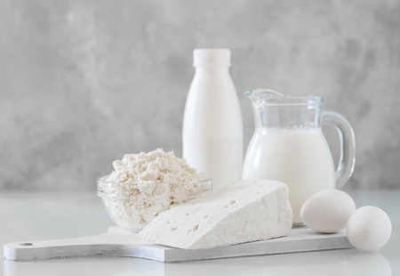 Homemade dairy products on white wooden surface, milk, cottage and feta cheese Stock Photo