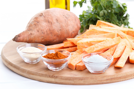 Raw sweet potatoes and spices, ingredients for baking on wooden cutting board Stock Photo