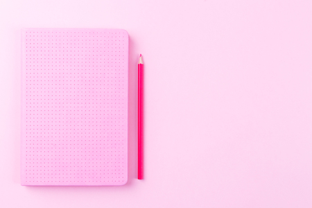 Diary or notepad with red pencil on pink background, flat lay, copy space