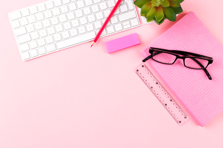 Student or freelancer workspace with keyboard, glasses, notepad, pen and succulent on pink background, flat lay. Space for text Stock Photo
