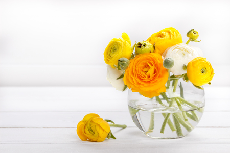 Bouquet of yellow ranunculus in a vase on white wooden background, copy space