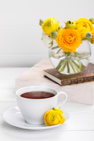 Cup of tea and yellow ranunculus on white wooden table Stock Photo