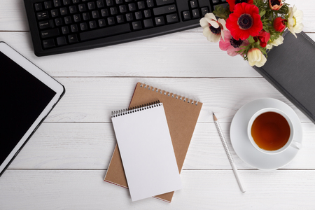 Empty notepad, cup of tea or coffee and office items on white desk, flat lay, top view