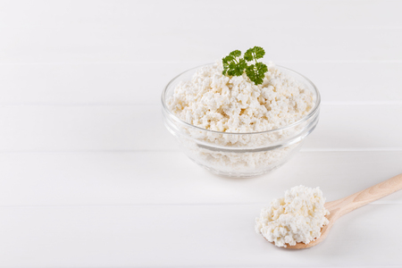 Homemade cottage cheese in a bowl on white old wooden table, copy space Stock Photo