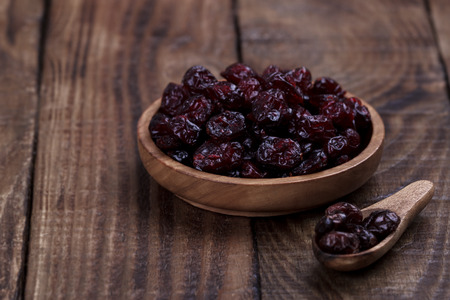 Organic raw dry cranberries in a bowl on dark wooden background