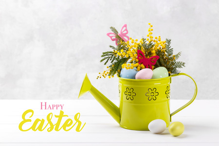 Colorful Easter eggs and mimosa flowers in decorative watering can on white wooden background, copy space Stock Photo