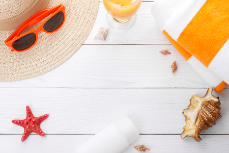 Beach accessories on white wooden background for summer vacation. Sunhat, sunglasses beach towel, sunburn lotion. Space for text.