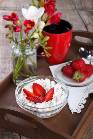 Healthy breakfast, cottage cheese with strawberries and cup of tea or coffee