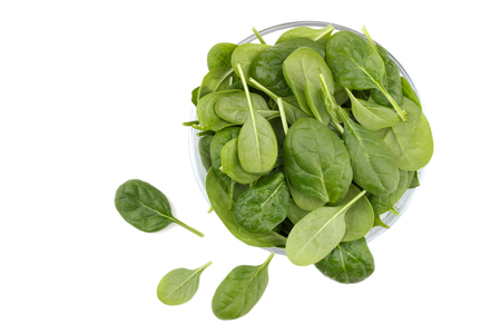 Fresh spinach in a glass bowl isolated over white background, close up, top view