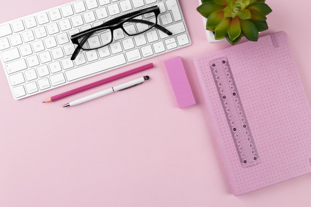 Workspace with keyboard, glasses, notepad, pen and succulent plant on pink background, flat lay.