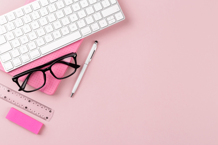 Workspace with keyboard, glasses, notepad and pen  on pink background, flat lay. Stock Photo