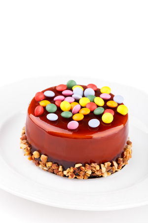 Caramel layered sponge cake with colorful sweet candies and nuts