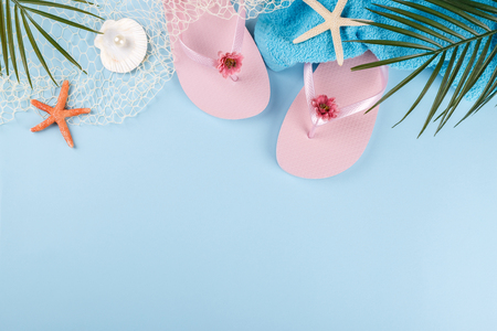 Summer holidays, pink beach slippers flip flops, palm tree branch and sea shells on blue background