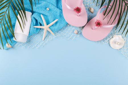 Summer holidays, pink beach slippers flip flops, palm tree branch, cream and sea shells on blue background Stock Photo
