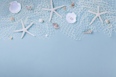 Summer flatlay, sea shells, fishnet and star fish a on blue background, copy space