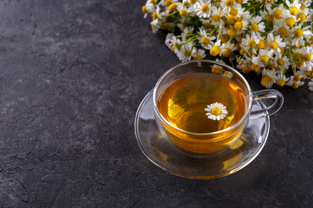 Healthy chamomile tea in a glass teacup on black stone background copy space Stock Photo