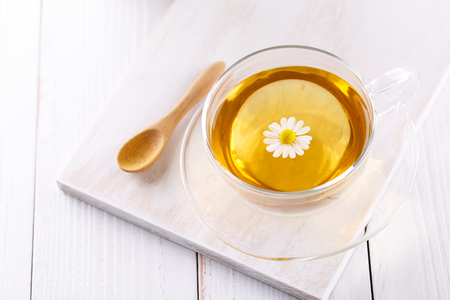 Healthy chamomile tea in a glass teacup on white wooden background copy space