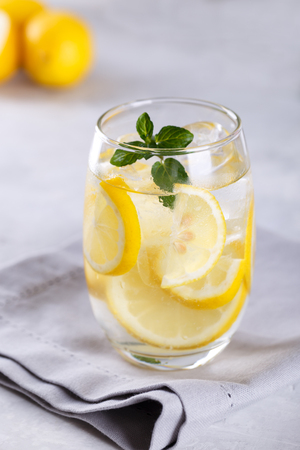 Citrus lemonade infused water with mint and lemon slices, healthy detox drink on grey stone background