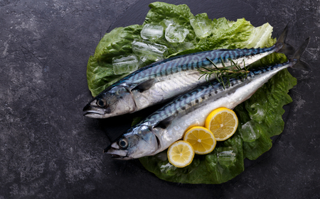 Raw Mackerel fish with lemon and spices on black stone background, top view copy space Stock Photo