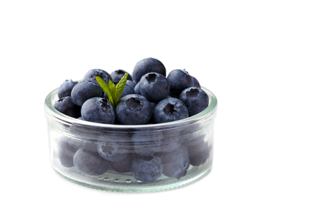 Hip of ripe blueberries in a glass bowl isolated over white