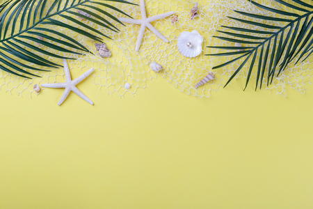 Summer flatlay, sea shells and palm tree branches on yellow background, copy space Stok Fotoğraf