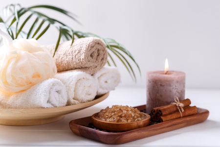 Spa setting with aromatic candle, coffee bath salt and soft cotton towels