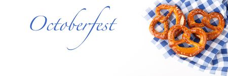 Traditional Bavarian salty pretzels on blue table cloth, close up banner for Octoberfest Stock Photo