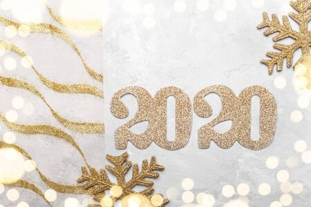New Year 2020 greetings card, golden numbers and snow flakes on grey background