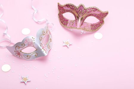 Carnival masks and confetti on pink background copy space close up