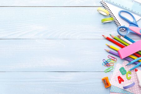 Back to school concept, with colorful stationery for kids on blue wooden background copy space Imagens