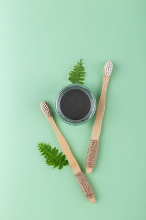 Natural bamboo tooth brushes and black dental powder on green background, zero waste products, natural oral hygiene