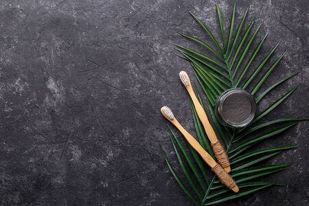 Natural bamboo tooth brushes and black dental powder on dark grey background, zero waste products, natural oral hygiene, copy space