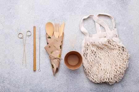 Zero waste bamboo tableware, eco friendly paper cup and napkin, straw, bag, wooden cutlery on natural stone background. Top view copy space