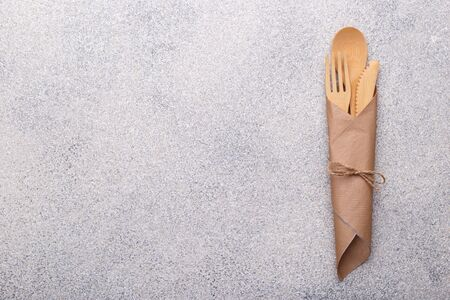 Zero waste bamboo tableware, eco friendly paper napkin and cups, wooden cutlery on natural stone background. Top view copy space 版權商用圖片