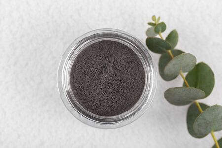 Black cosmetic clay powder for skin and hair, spa and wellness, natural cosmetics on white background