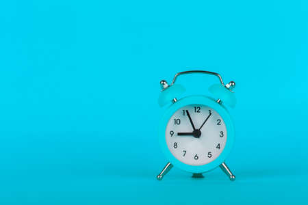 Small alarm clock on blue background, ringing five minutes to nine, copy space 版權商用圖片